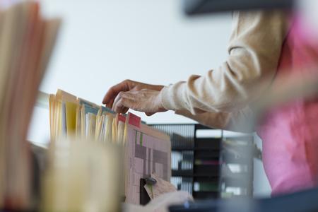 Senior woman looking through filing cabinet LANG_EVOIMAGES