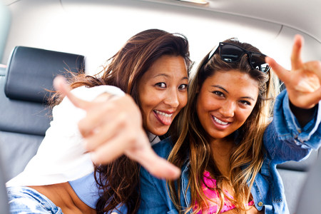 jesting: Two female friends making hand gestures in car