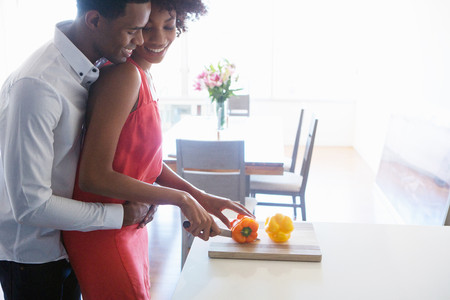 afro caribbean ethnicity: Young woman chopping peppers,man with arms around her LANG_EVOIMAGES