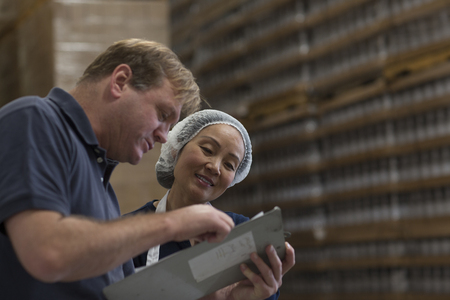 check ups: Factory worker and manager looking at clipboard in warehouse