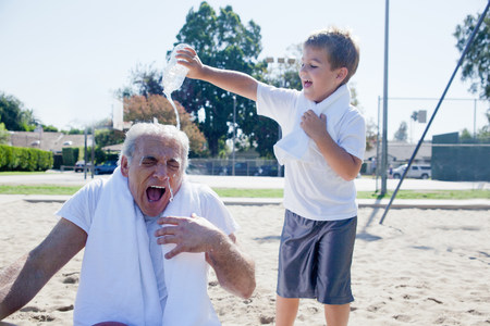 silliness: Boy pouring water on grandfather