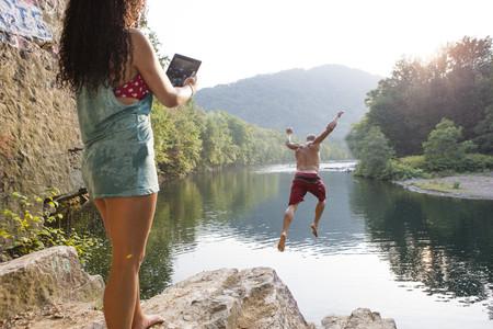 buen vivir: Mujer fotografiando novio saltando de roca saliente, Hamburgo, Pensilvania, Estados Unidos
