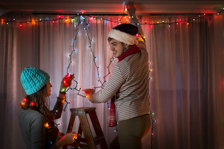 housing lot: Young couple putting up fairy lights at christmas