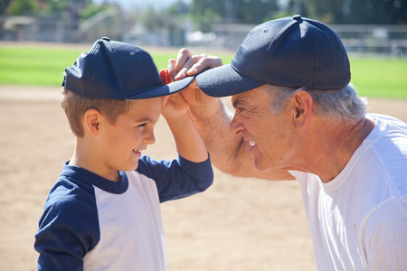 Boy and grandfather in baseball caps,face to face LANG_EVOIMAGES