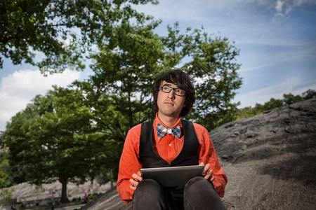 kooky: Young man sitting on rocks using tablet