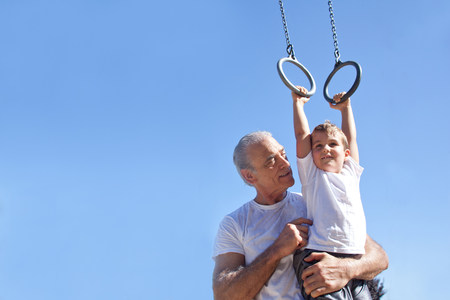 exerting: Grandfather holding grandson on gymnastic rings