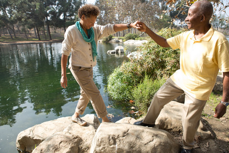 65 70 years: Portrait of senior couple stepping on rocks by lake in park