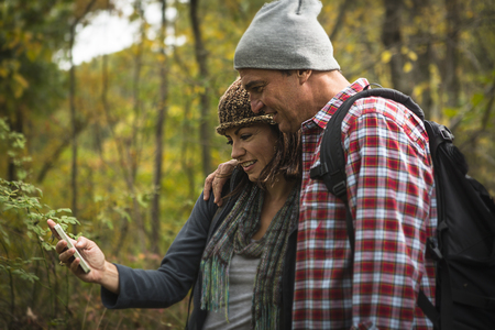 Mature couple taking self portrait photograph on smartphone in forest LANG_EVOIMAGES