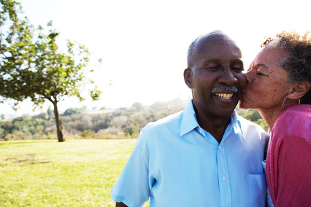 65 70 years: Senior woman kissing man on cheek LANG_EVOIMAGES