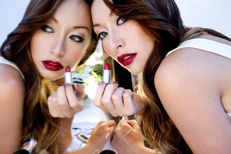 desconfianza: Mujer que aplica el lápiz labial en espejo