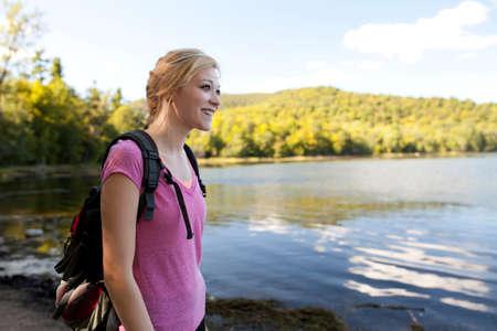 exerting: Woman walking beside lake