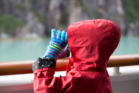 Young girl looking at glacier in Alaska from cruise ship,Ketchikan,Alaska,USA