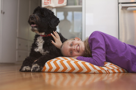 Portrait of girl lying on cushion with pet dog LANG_EVOIMAGES