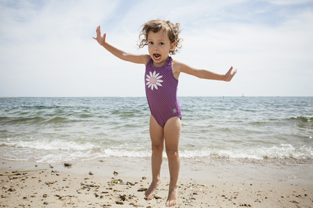 Portrait of jumping female toddler on beach at Falmouth, Massachusetts, USA LANG_EVOIMAGES