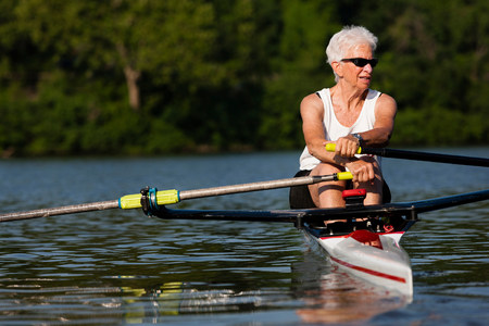 impulsive: Senior woman rowing in rowing boat