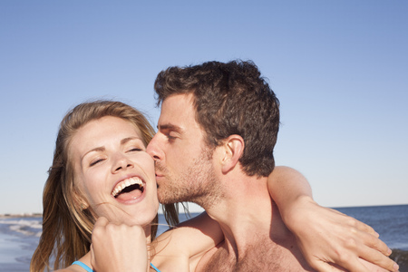 smooching: Close up portrait of couple on beach,Breezy Point,Queens,New York,USA