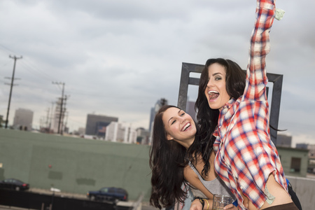 jesting: Two female friends jumping around at rooftop party