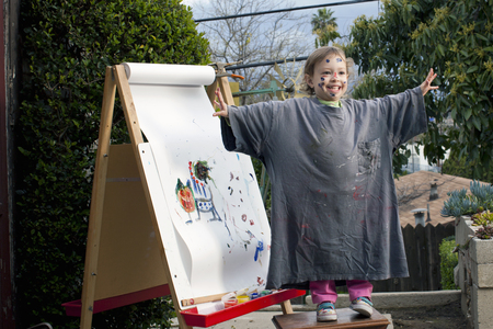 untidiness: Girl outdoors painting on easel LANG_EVOIMAGES