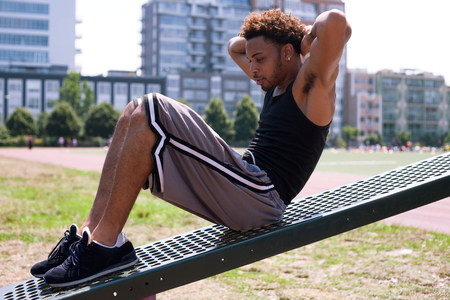 Young man doing sit-ups at outdoor gym
