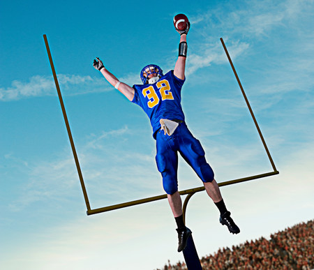 American footballer jumping to catch ball in front of goal LANG_EVOIMAGES