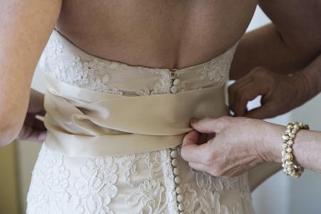 milestones: Bride being helped to get into wedding dress