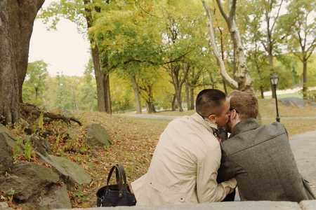 mirroring: Man kissing partner on cheek in park