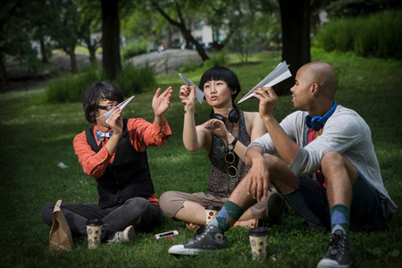 woman hanging toy: Three friends holding paper planes in park LANG_EVOIMAGES