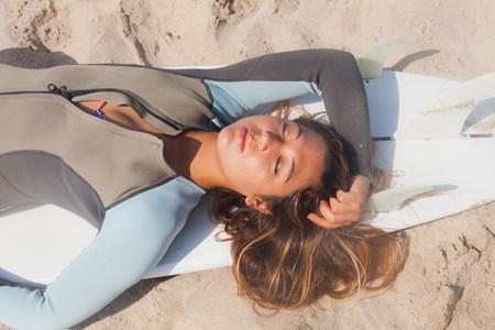 shutting: Young woman sunbathing on surfboard,Hermosa Beach,California,USA