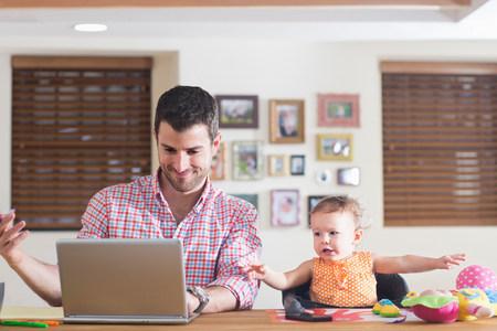 relaciones laborales: Hombre trabajando en el mostrador de la cocina con el bebé sentado al lado