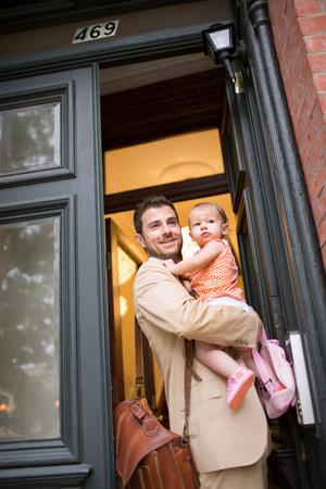 towerblock: Man holding baby standing at front door