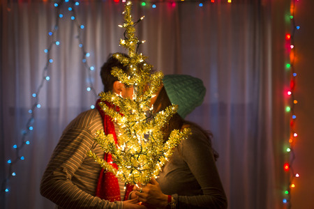 Young couple kissing behind illuminated christmas tree