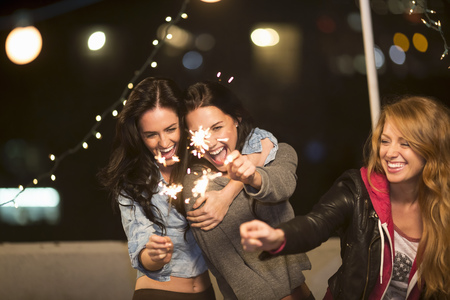 3 persons only: Female friends with sparklers at rooftop party