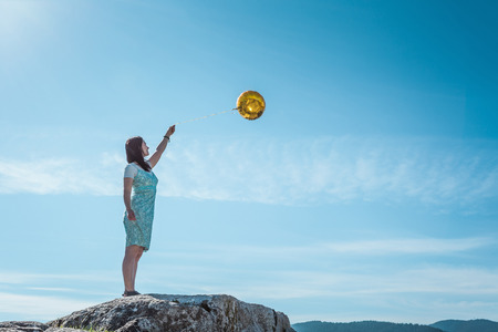 expect: Mature woman standing on rock with golden balloon