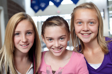 Close up portrait of three teen and pre-adolescent girls smiling LANG_EVOIMAGES