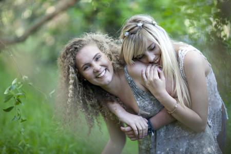 Two teenage girls having fun in woodland