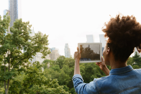 afro caribbean ethnicity: Woman using digital tablet to photograph