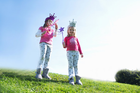 Two young sisters dressed up as fairies standing on hill