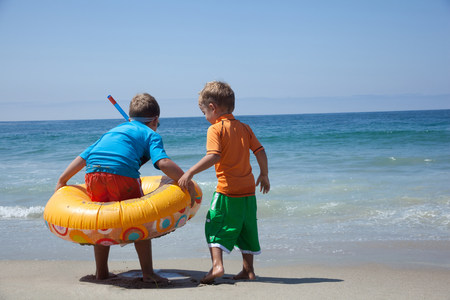 Two young brothers playing with rubber ring at beach