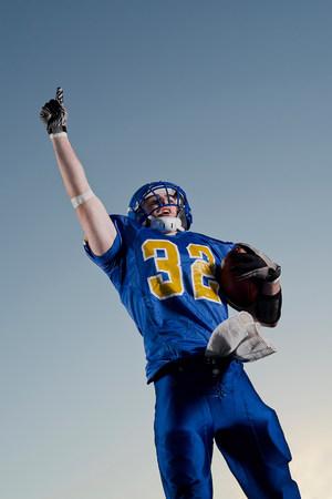 strip shirt: American footballer pointing towards sky