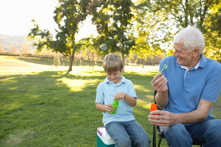 shutting: Grandfather and grandson blowing bubbles