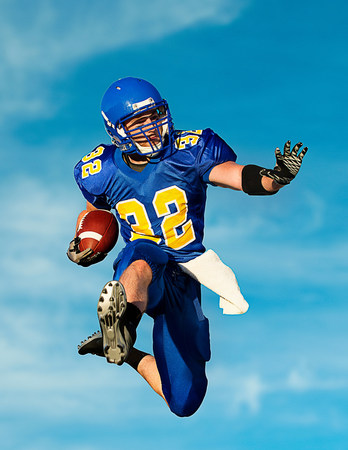 American footballer with ball against blue sky LANG_EVOIMAGES