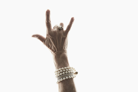 65 69 years: Studio shot of mature womans hand making gesture