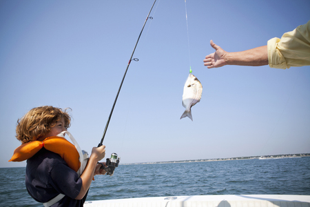 65 69 years: Boy reeling in fish on boat,  Falmouth, Massachusetts, USA LANG_EVOIMAGES
