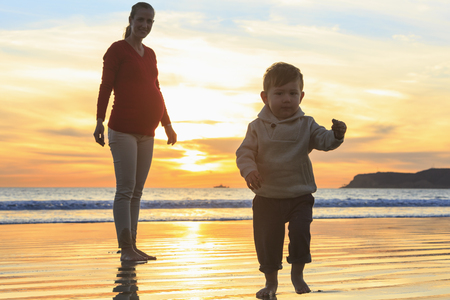 level playing field: Mother and toddler son playing on beach, San Diego, California, USA