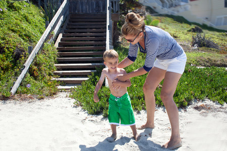 getting out: Mother applying sun cream to toddler at beach