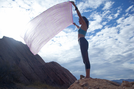 aging american: Woman standing at Vazquez Rocks holding sheet up