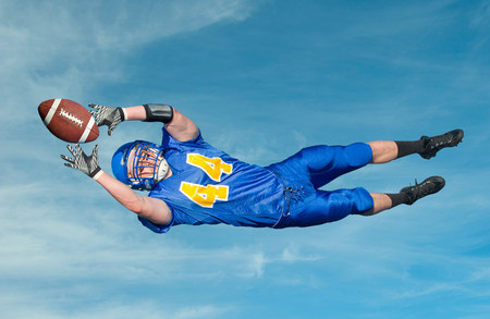American footballer catching ball against blue sky