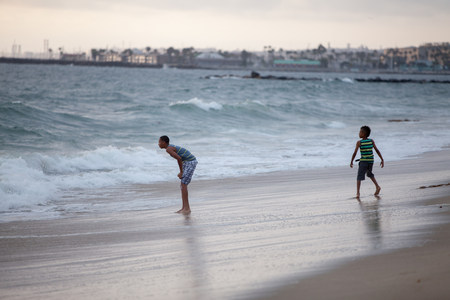 Two boys playing on Huntington Beach,California,USA