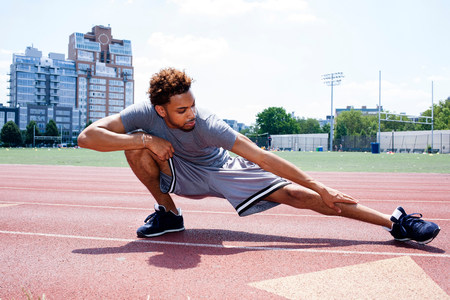 Young man stretching leg on running track