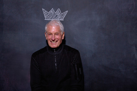 top animated: Portrait of senior man in front of chalked crown on blackboard